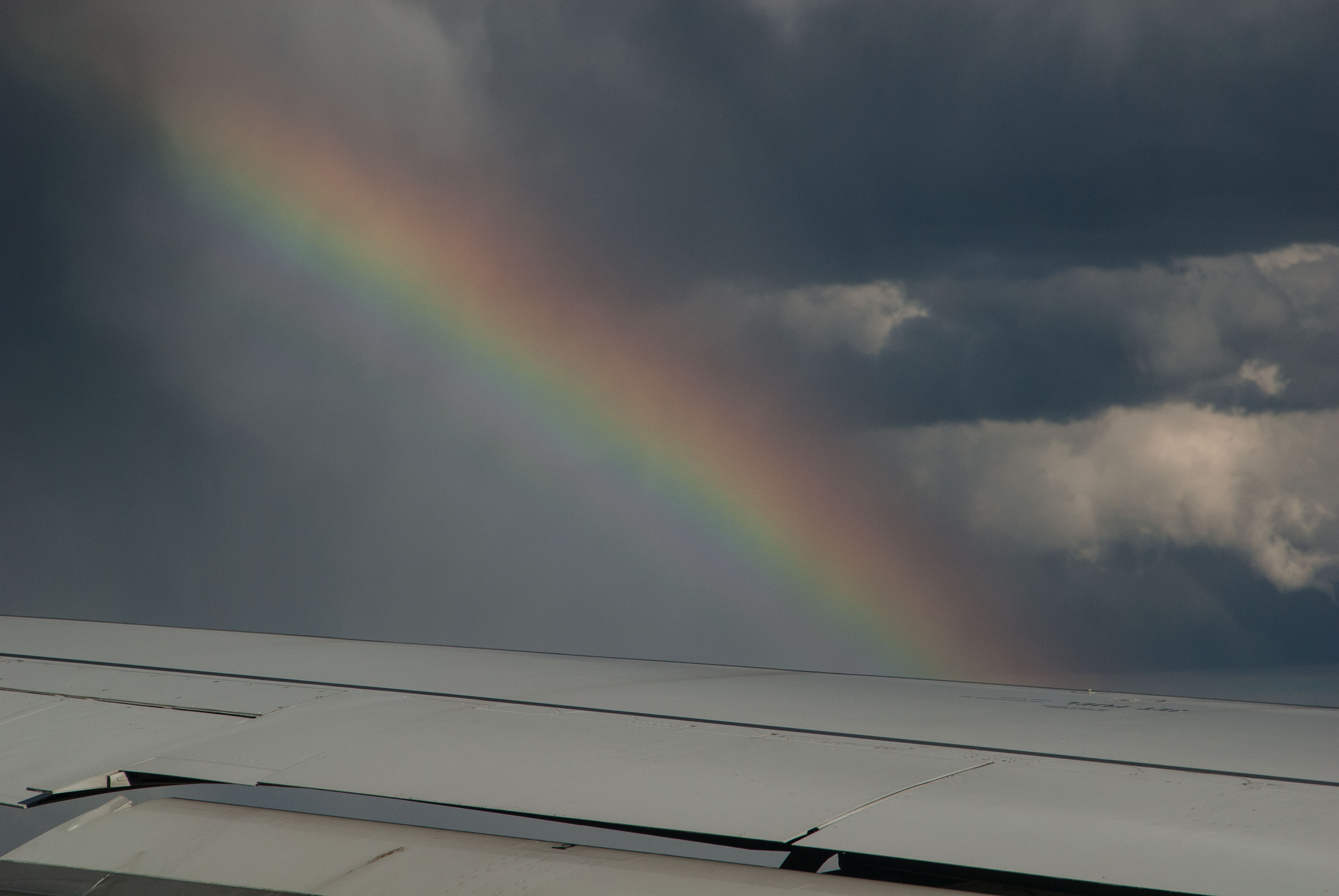Airplane in clouds with rainbow