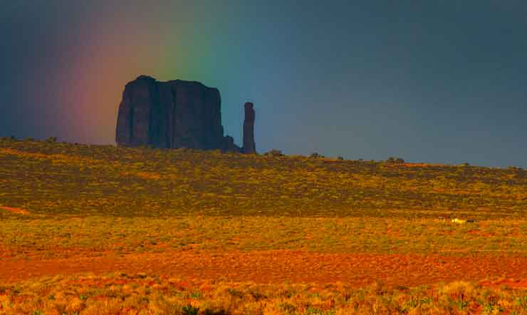 A rainbow hovers over West Mitten Butte at Monument Valley on the Navajo Nation in northern Arizona