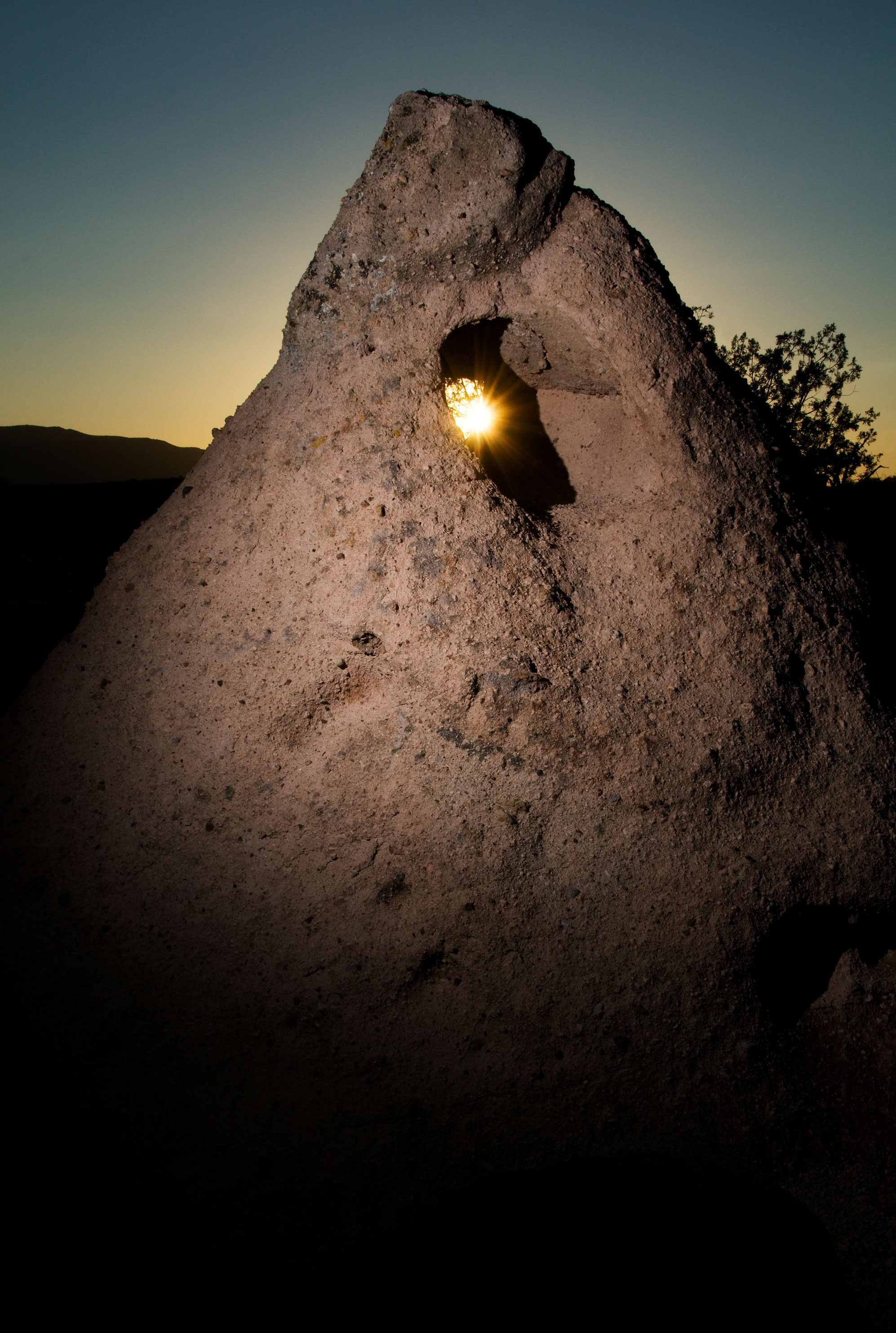 The sun setting behind a Tee Pee rock formation near Camp Verde, Arizona